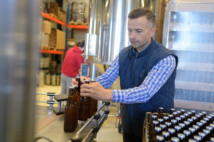 Factory operative packing bottles from end of production line